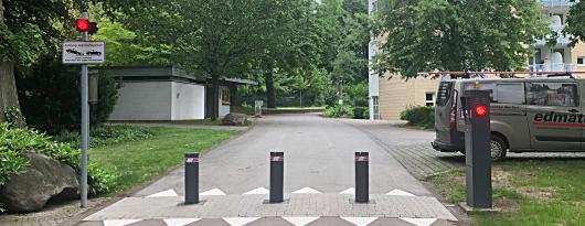 Drei, hellgrau pulverbeschichtete Automatikpoller mit gleichfarbigem Pollerdeckel sichern ein privates Grundstück.