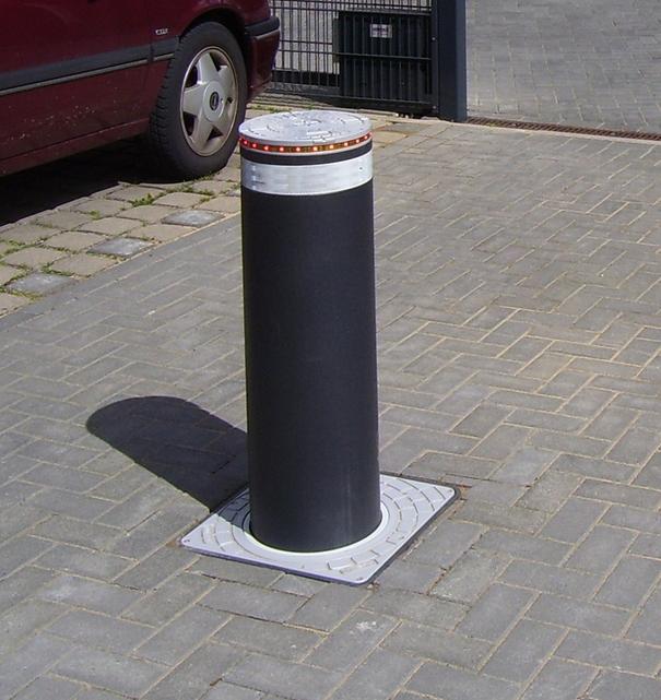 Dunkelgrauer Poller mit weißem Reflexband und roten LEDs im Pollerdeckel. Standort Isernhagen.