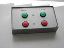Bedientableau in grauem Kunststoffgehäuse und je zwei grünen und zwei roten Tastern.